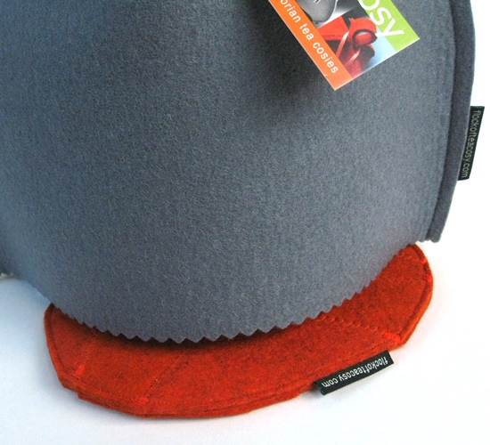 Small modern tea cosy atop a reversible teapot trivet in wool felt
