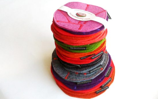 Stack of colourful wool felt coasters, eco concious and stylish.